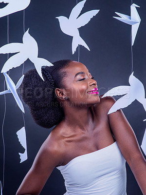 Buy stock photo Studio shot of a beautiful young woman posing with paper birds against a black background