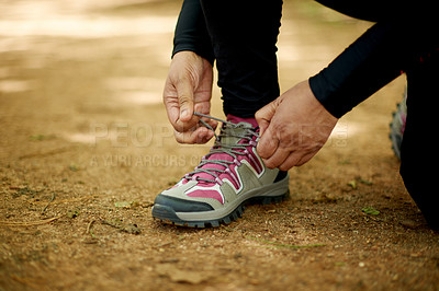Buy stock photo Shot of an unrecognisable woman tying her shoelaces before a jog out in nature