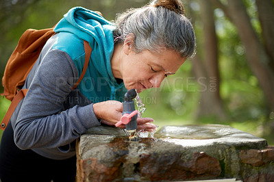 Buy stock photo Shot of a mature woman drinking water from a fountain while going for a hike in nature