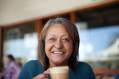 Buy stock photo Shot of a mature woman having a cup of coffee at a cafe