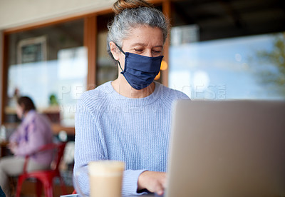 Buy stock photo Shot of a masked mature woman using a laptop at a cafe
