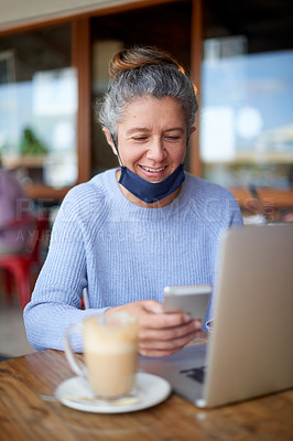Buy stock photo Shot of a mature woman using a laptop and smartphone at a cafe with a mask around her neck