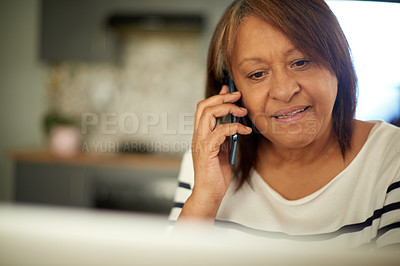 Buy stock photo Shot of a mature woman talking on her cellphone while sitting at home with her laptop