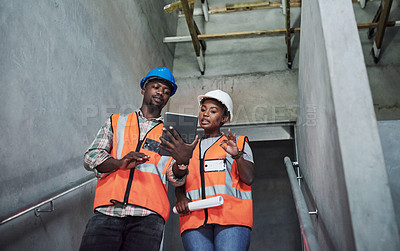 Buy stock photo Shot of a young man and woman using a digital tablet while working at a construction site