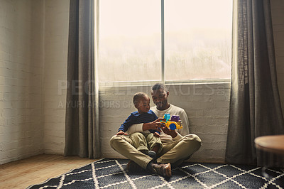 Buy stock photo Shot of a young man playing with son at home