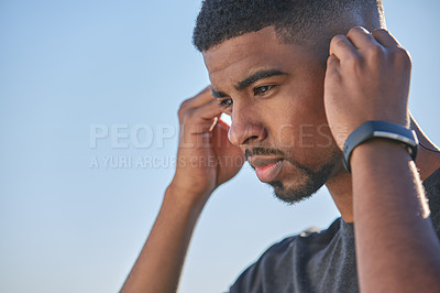 Buy stock photo Shot of a sporty young man wearing earphones while exercising outdoors