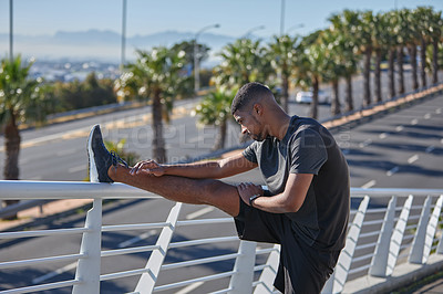 Buy stock photo Shot of a sporty young man stretching his legs while exercising on a bridge in the city