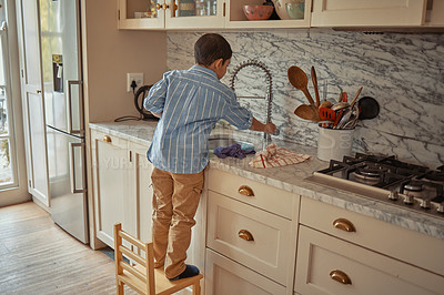 Buy stock photo Shotof a young boy doing the dishes at home