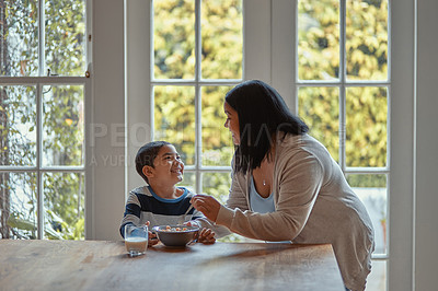 Buy stock photo Shot of a young woman serving her son breakfast at home