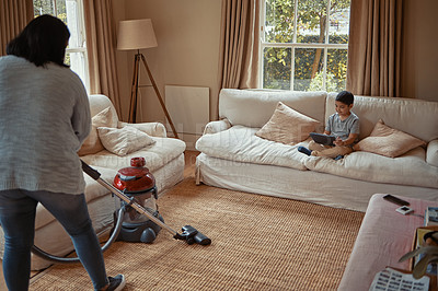 Buy stock photo Shot of a woman vacuuming while her son sits on the couch