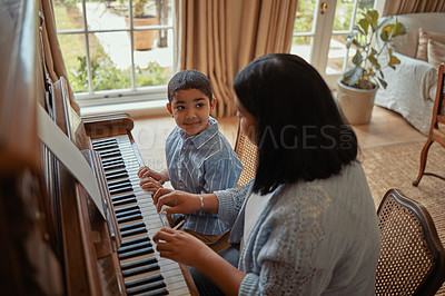 Buy stock photo Cropped shot of a young mother playing the piano with her son