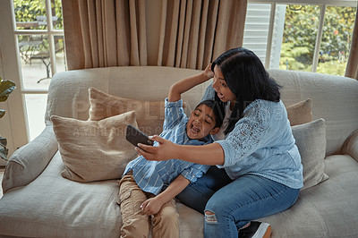 Buy stock photo Shot of a young woman taking a selfie with her son while sitting at home