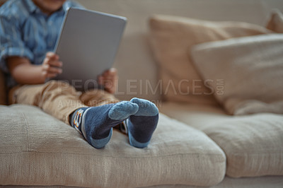 Buy stock photo Cropped shot of a little boy using a digital tablet while sitting on the couch