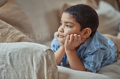 Buy stock photo Cropped shot of a young boy looking thoughtful while lying on the couch at home