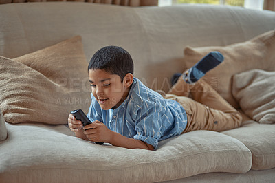 Buy stock photo Shot of a young boy holding a remote control while lying on the couch at home
