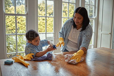 Buy stock photo Shot of a young boy helping his mother with the chores at home