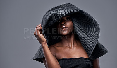 Buy stock photo Shot of a young woman wearing a oversized sunhat against a grey background