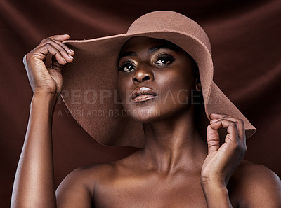 Buy stock photo Shot of a beautiful young woman wearing a hat while posing against a brown background