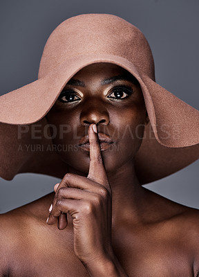 Buy stock photo Shot of a young woman wearing a hat and posing with her finger on her lips against a grey background
