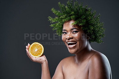 Buy stock photo Shot of a beautiful woman holding an orange and wearing a leaf wreath on her head
