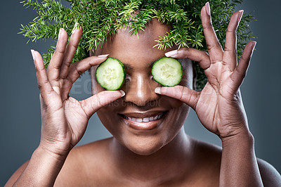 Buy stock photo Shot of a woman holding cucumber slices over her eyes while wearing a leaf wreath