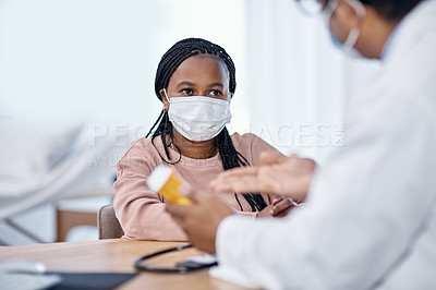 Buy stock photo Shot of a young woman receiving medication from a doctor during a consultation