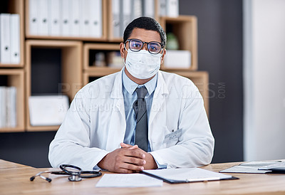 Buy stock photo Portrait of a young doctor wearing a face mask while working in his office