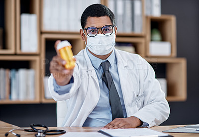 Buy stock photo Portrait of a young doctor holding a bottle of pills in his office
