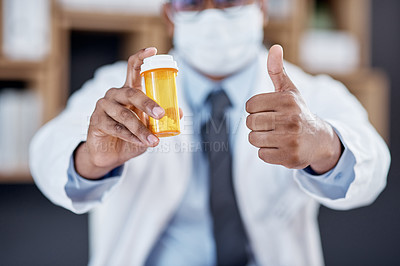 Buy stock photo Closeup shot of an unrecognisable doctor holding a bottle of pills and showing thumbs up in his office