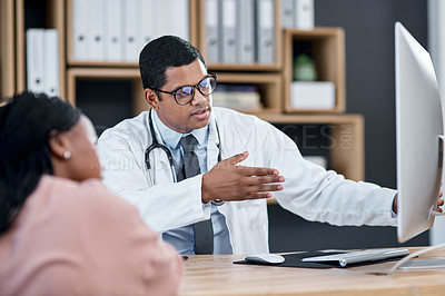 Buy stock photo Shot of a doctor using a computer while having a consultation with a patient