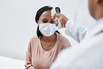 Buy stock photo Shot of a young woman getting her temperature taken with an infrared thermometer by a doctor