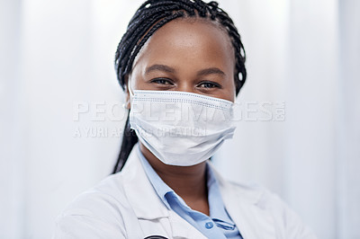 Buy stock photo Portrait of a young doctor wearing a face mask while working in a hospital