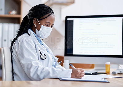 Buy stock photo Shot of a young doctor writing notes while working in her office