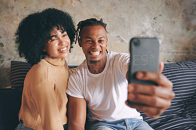 Buy stock photo Shot of a young couple taking selfies together at home
