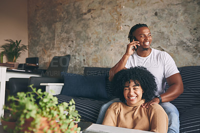 Buy stock photo Shot of a young man talking on a cellphone while relaxing with his girlfriend at home