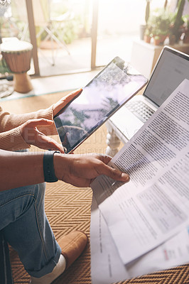 Buy stock photo Closeup shot of an unrecognisable couple using a digital tablet while going through paperwork together at home