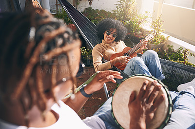 Buy stock photo Shot of a young woman playing ukulele while her boyfriend plays drums