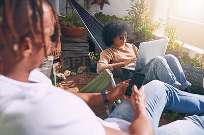 Buy stock photo Shot of a young woman using a laptop and relaxing on a hammock while her boyfriend uses a cellphone