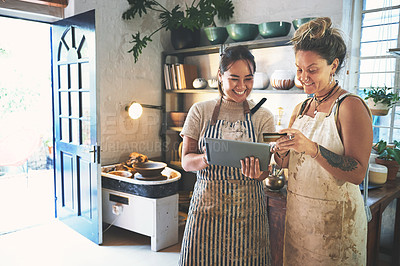 Buy stock photo Shot of two young women using a digital tablet and credit card while working together in a pottery studio
