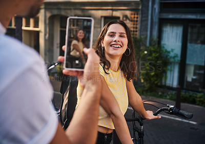 Buy stock photo Shot of a man taking a picture of his girlfriend with a smartphone while exploring the city of Amsterdam