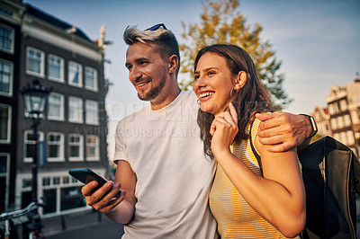 Buy stock photo Shot of a young couple using a smartphone while exploring the city of Amsterdam