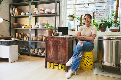 Buy stock photo Full length portrait of an attractive young business owner sitting alone in her pottery studio with her arms folded