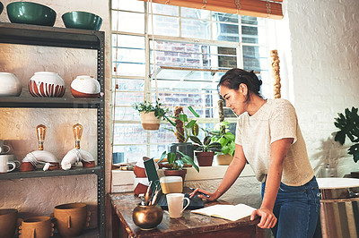 Buy stock photo Cropped shot of an attractive young business owner standing and using her laptop in her pottery studio