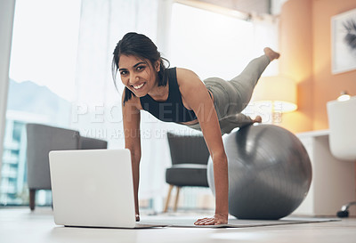 Buy stock photo Shot of a woman working out in her living room with her laptop in front of her