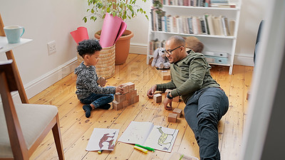 Buy stock photo Shot of an adorable little boy and his father playing with wooden blocks on the floor at home