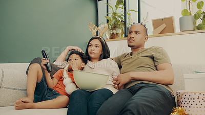 Buy stock photo Shot of a family of three watching a movie and eating popcorn during Christmas time