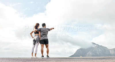 Buy stock photo Rearview shot of a sporty young man and woman looking at the view while exercising outdoors