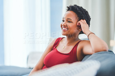 Buy stock photo Cropped shot of a young lady smiling with her hand against her head while sitting on the sofa in her apartment