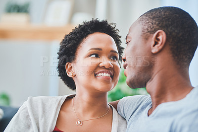 Buy stock photo Cropped shot of a young loving couple looking endearingly at each other in their apartment