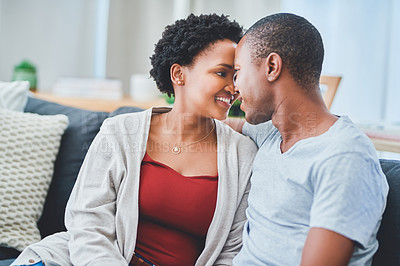 Buy stock photo Cropped shot of a young loving couple looking endearingly at each other while sitting on the couch in their apartment